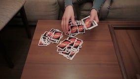 La muchacha comparte una cubierta de tarjetas entre tres jugadores almacen de video