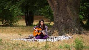 La muchacha compone música con una guitarra almacen de video