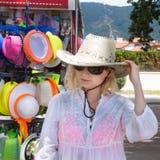 La muchacha compra el sombrero en centro turístico fotos de archivo