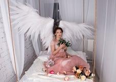 La muchacha con ángel abierto se va volando sentarse en cama de la ejecución fotos de archivo