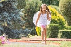 La muchacha con ángel se va volando el funcionamiento alrededor en la lluvia en el jardín Imagenes de archivo