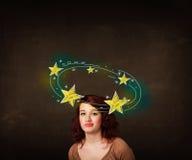 La muchacha con amarillo protagoniza circleing alrededor de su cabeza Imagenes de archivo