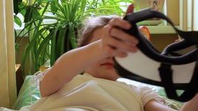 La muchacha con ARG en los movimientos cabeza y manos que mienten en cama, entonces saca ARG almacen de metraje de vídeo