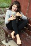 La muchacha con base desnuda del adolescente con la taza de té se sienta en banco Fotografía de archivo