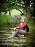 La muchacha con la cámara se sienta en los pasos del vintage en un parque verde fotos de archivo libres de regalías