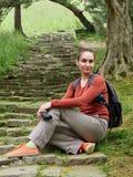 La muchacha con la cámara se sienta en los pasos del vintage en un parque verde imagenes de archivo