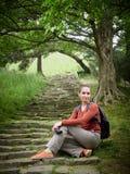 La muchacha con la cámara se sienta en los pasos del vintage en un parque verde imagen de archivo libre de regalías