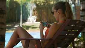 La muchacha con la cola de caballo charla en el teléfono en silla plegable
