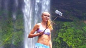 La muchacha con la cola de caballo hace el selfie contra la cascada hermosa almacen de metraje de vídeo