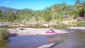 La muchacha con la cola de caballo hace yoga en piedra entre el río almacen de video