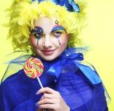 La muchacha con con maquillaje creativo sostiene el lollipop Fotos de archivo