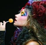 La muchacha con con maquillaje creativo sostiene el lollipop Foto de archivo