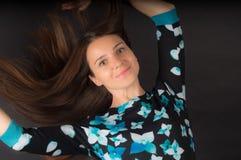 La muchacha con desarrollar el pelo largo en fondo negro imagen de archivo