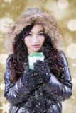 La muchacha con el abrigo de invierno disfruta de la bebida caliente Imágenes de archivo libres de regalías