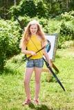 La muchacha con el arco y las flechas cerca del deporte apunta Imagen de archivo
