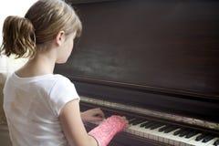 La muchacha con el brazo quebrado juega el piano Imagen de archivo libre de regalías