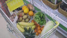 La muchacha con el carro del ultramarinos coge verduras y las frutas almacen de video