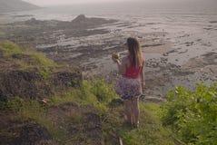 La muchacha con el coco mira la hermosa vista Fotos de archivo