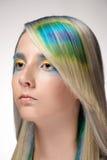 La muchacha con el colorante de pelo profesional y creativos componen en estilo del pavo real Foto de archivo libre de regalías