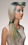 La muchacha con el colorante de pelo profesional y creativos componen en estilo del pavo real Foto de archivo