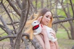La muchacha con el conejo blanco Mujer hermosa que sostiene una liebre foto de archivo libre de regalías