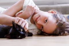 La muchacha con el gato en el piso Imagen de archivo