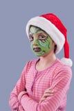 La muchacha con el grinch tiene gusto de la pintura de la cara. Imagen de archivo