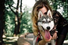 La muchacha con el husky siberiano Juegos deliciosos de la muchacha con un husky siberiano Muchacha que camina con un perro de bú foto de archivo