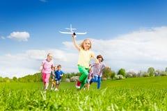 La muchacha con el juguete del aeroplano corre rápidamente y embroma detrás Imagenes de archivo