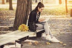 La muchacha con el libro que se sienta debajo del árbol Foto de archivo libre de regalías