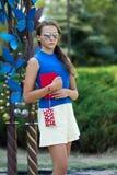 La muchacha con el libro rojo y un bolso rojo Fotos de archivo