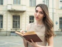 La muchacha con el libro y los tulipanes amarillos en ciudad parquean la lectura Imagenes de archivo