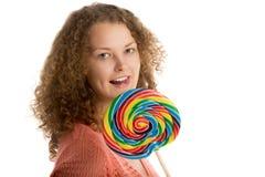 La muchacha con el lollypop gigante se lame los labios Fotografía de archivo libre de regalías