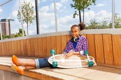 La muchacha con el monopatín se sienta en la construcción de madera Foto de archivo
