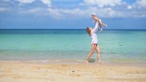 La muchacha con el niño va en paseos y juego en la playa durante día soleado metrajes