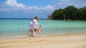 La muchacha con el niño va en paseos y juego en la playa durante día soleado almacen de metraje de vídeo