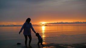 La muchacha con el niño va para los paseos y el juego en la playa en el tiempo de la puesta del sol metrajes