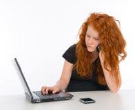 La muchacha con el ordenador está llamando Imagen de archivo