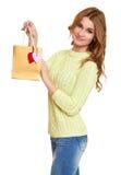 La muchacha con el panier y los corazones vistieron vaqueros y un suéter verde que presentaba en estudio en el fondo blanco Foto de archivo