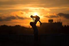 La muchacha con el papá que camina en silueta de la puesta del sol Fotografía de archivo