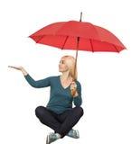 La muchacha con el paraguas rojo se sienta a piernas cruzadas Fotos de archivo libres de regalías