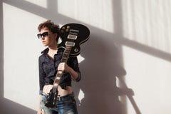 La muchacha con el pelo corto con una guitarra fotos de archivo