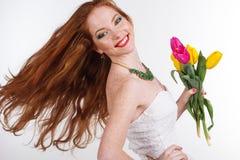 La muchacha con el pelo del vuelo está sosteniendo el ramo de tulipanes Fotografía de archivo libre de regalías