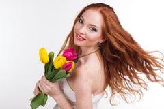 La muchacha con el pelo del vuelo está sosteniendo tulipanes coloridos Fotografía de archivo