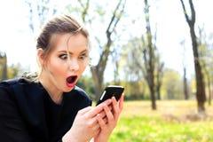 La muchacha con el pelo despeinado y la boca abierta mira fijamente en smartphone Foto de archivo libre de regalías
