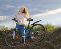 La muchacha con el pelo hermoso en una bicicleta Fotos de archivo