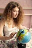 La muchacha con el pelo largo busca algo en el globo Foto de archivo