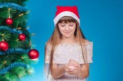 La muchacha con el pelo largo en un casquillo del rojo cuesta cerca de un árbol del Año Nuevo Foto de archivo libre de regalías