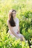 La muchacha con el pelo largo hermoso se está sentando en el claro Imágenes de archivo libres de regalías
