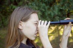 La muchacha con el pelo largo mira a través de un telescopio parque, al aire libre El concepto del futuro imagenes de archivo